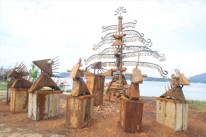"""面对大海的生命之树,12根树枝代表12个月份,7匹马代表一星期7天和彩虹的7种颜色。每当海风吹来,铁罐碰撞出悦耳交响曲。这个名为""""起义""""的装置艺术由Sivarajah Natarajan构想制作,材料皆来自生活中的废置物。"""