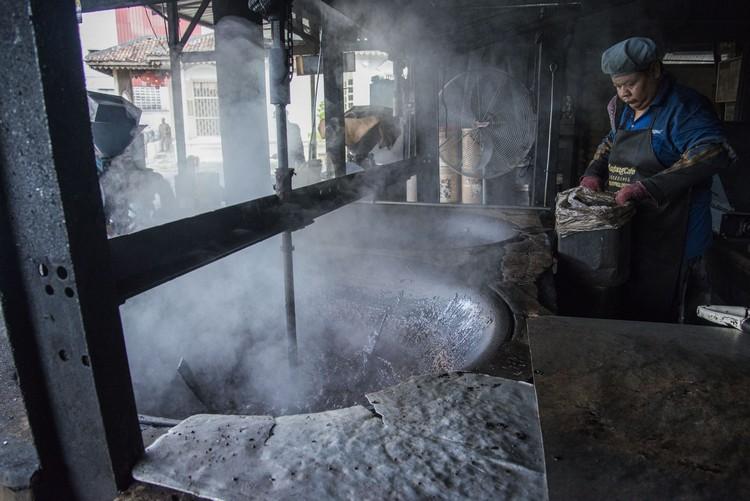 3. 把糖、油及咖啡豆倒入大锅,进行炒糖动作,并非要甜,而是让咖啡豆有股焦香味。