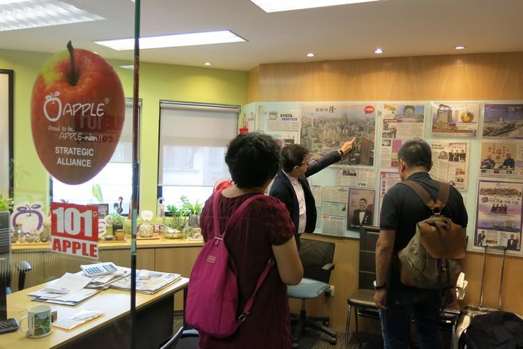 透过报章鸟瞰图向诸位贵宾指出蘋果大楼所在位置。