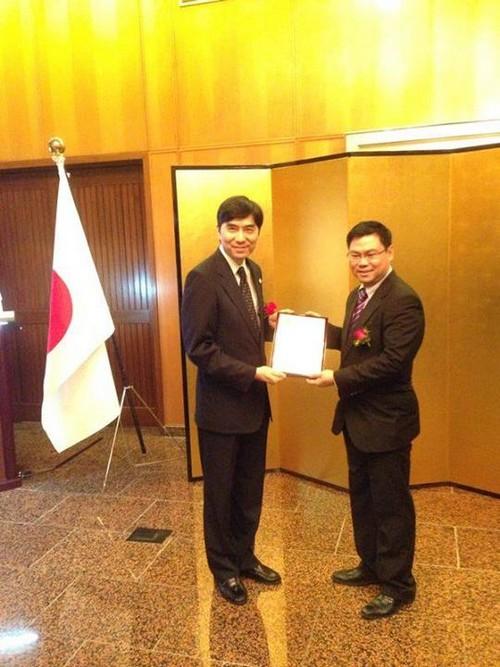 日本驻新加坡大使竹内春久(左),将奖项颁发给新加坡新加坡蘋果旅遊执行董事张炳珊(右)。