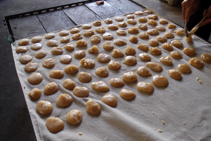 将在半液体状态同时,用人工弄成一致的份量,等待它干后变成椰糖饼就大功告成了.