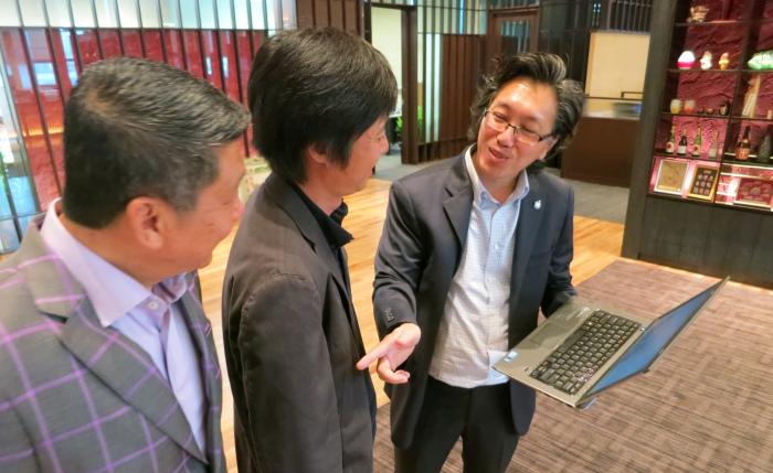 Koh san向须藤 利宗展示蘋果101网络旅游杂志。