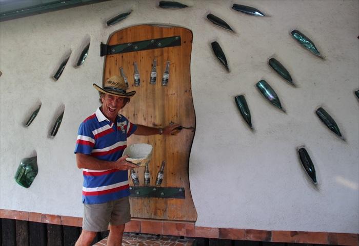 """大茉莉休闲农场主人吴连春的丈夫罗约翰使用酒瓶作为""""报纸屋""""的美化工作。"""