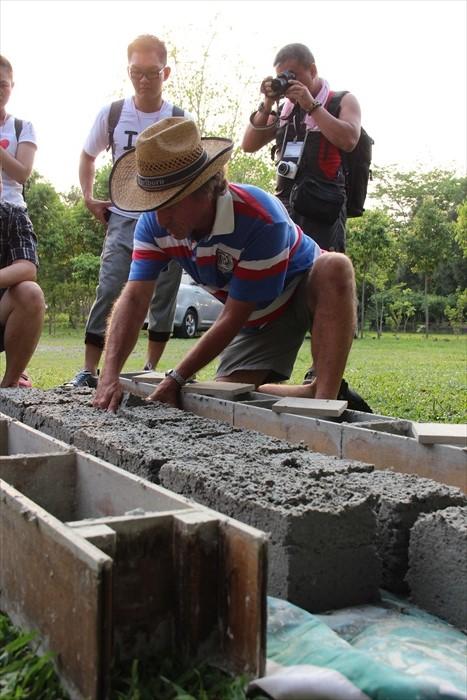 罗约翰在示范使用旧报纸及采用水泥混合成泥浆制出的砖块过程。