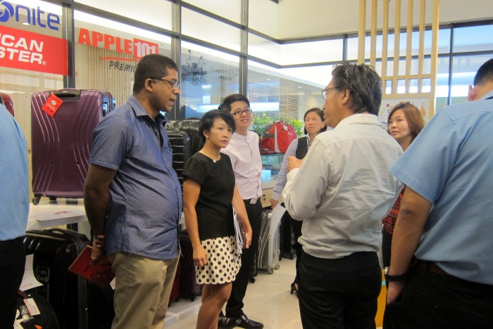 蘋果旅遊集团副董事经理拿督斯里许育兴(右)向Dato Bernard解释蘋果101礼品兑换的运作。