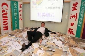 """""""看星洲.找蘋果.圆旅梦""""的读者反应非常踊跃,李益辉躺卧在参赛表格堆中,并从中抽出获得终极至尊旅游大奖的幸运儿!"""