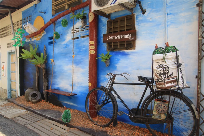 真实的旧式脚踏车,后座载着一大包用汽水铝罐做成的榴莲,摆姿势拍人画合一立体照尤佳。