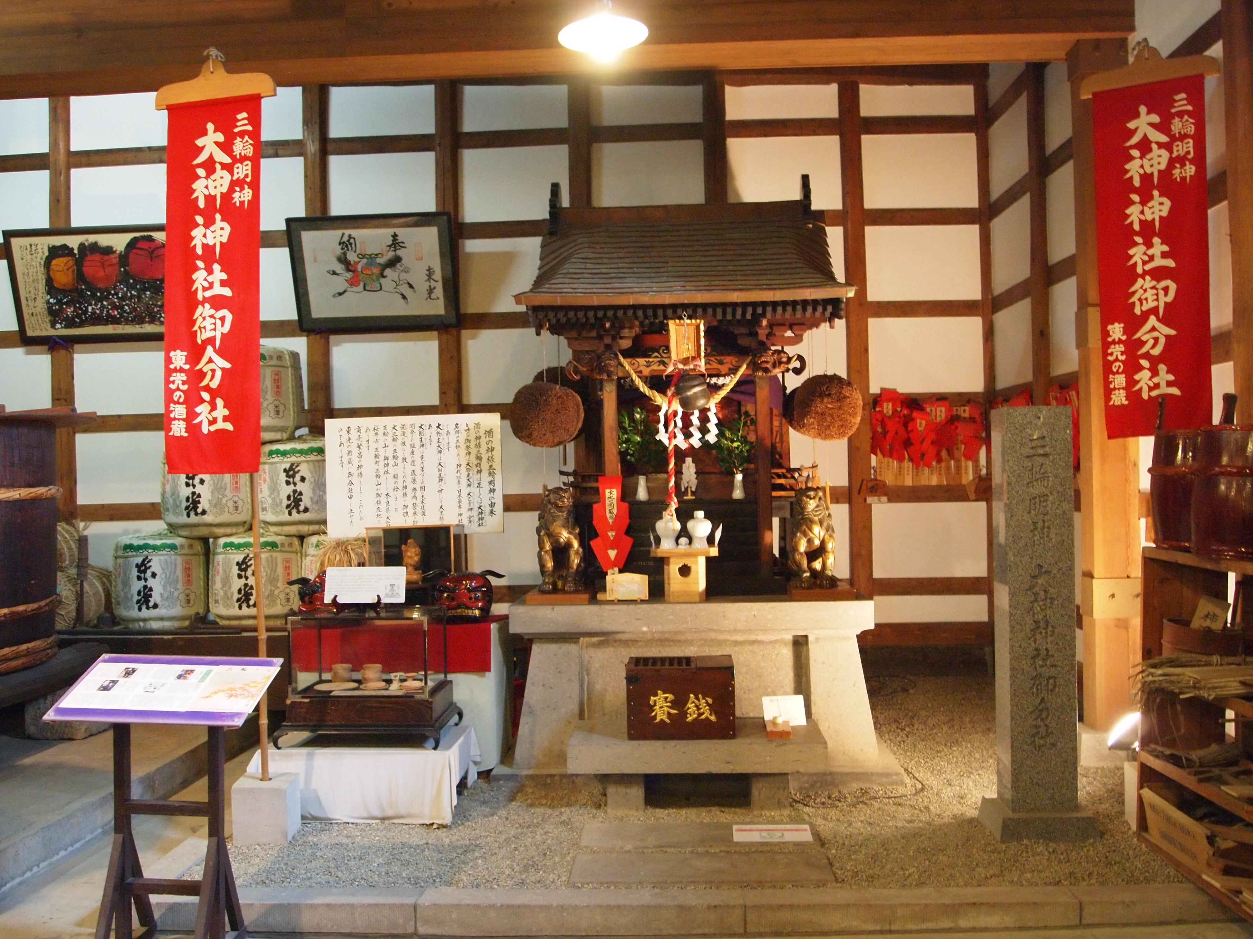 """在资料馆内的奈良县大神神社御分社,供奉着日本酒的守护神三轮明神,图中可看见日本酒蔵屋檐下都会掛着用杉树的枝叶紮成的球状物,日本人称之为杉玉(Sugitama),""""杉""""指的是象征酒神的杉树, """"玉"""" 在日文中指的是球或圆状的东西,是日本自古以来酒蔵的标记,当新酒好的时候,造酒人家会把新绿的杉玉掛出来,让大家知道新酒已经酿好了,等到杉玉逐渐枯干变成褐色时,就表示酒已经熟成,大家可以来买酒了!"""