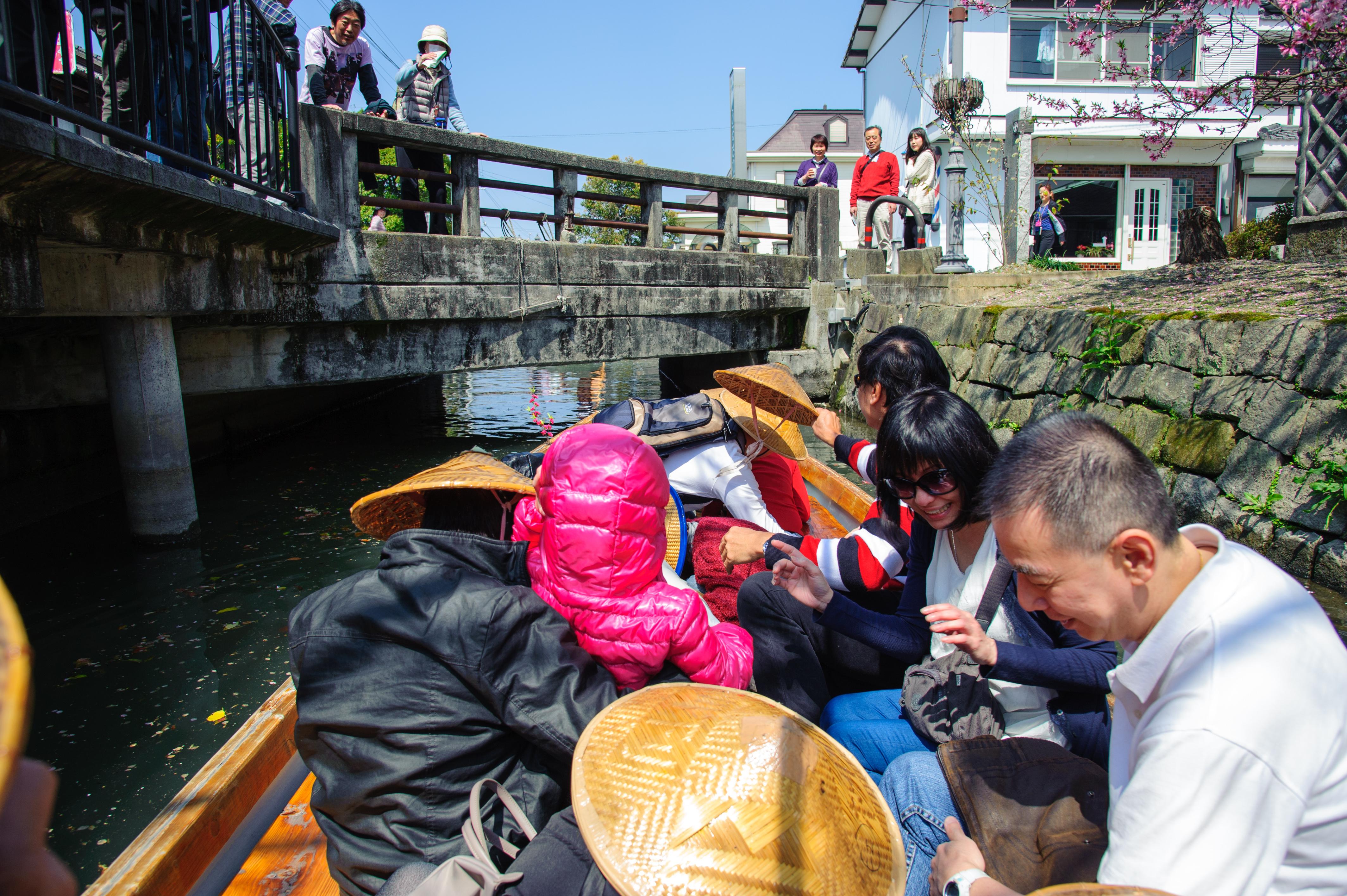 小船经过矮桥,乘客得配合低头才可穿过。