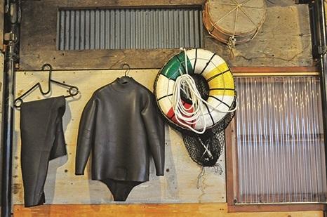 墙上挂着的是海女们潜入海里作业的工具,如今也改穿潜水衣了。