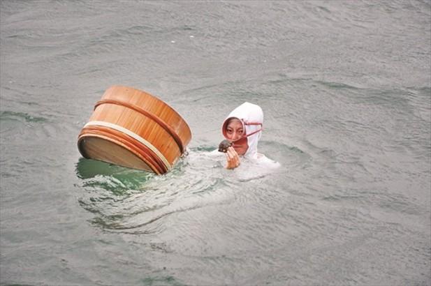 海女成功从海底捞起海鲜了,看海女手中拿着的是什么?