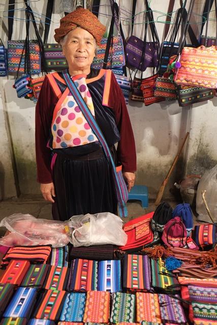 穿着传统服饰的婆婆售卖民族特色的小包包。