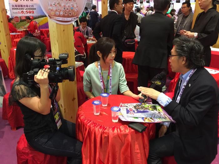 记者梁宝义和郑佳雯在旅展中搜集大众与旅游业者的意见。