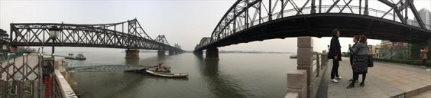 """中国丹东鸭绿江上的""""中朝友谊桥(左)与""""鸭绿江断桥,见证了历史;对面就是朝鲜多新义州。"""