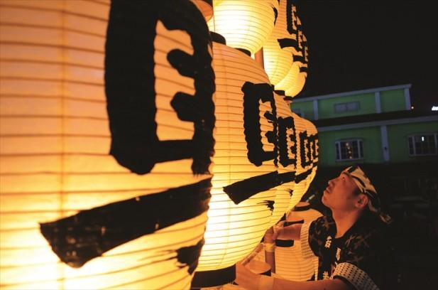 """重约50公斤的竿灯称作""""大若"""",表演者需时时留意不让灯笼内的火熄灭。"""
