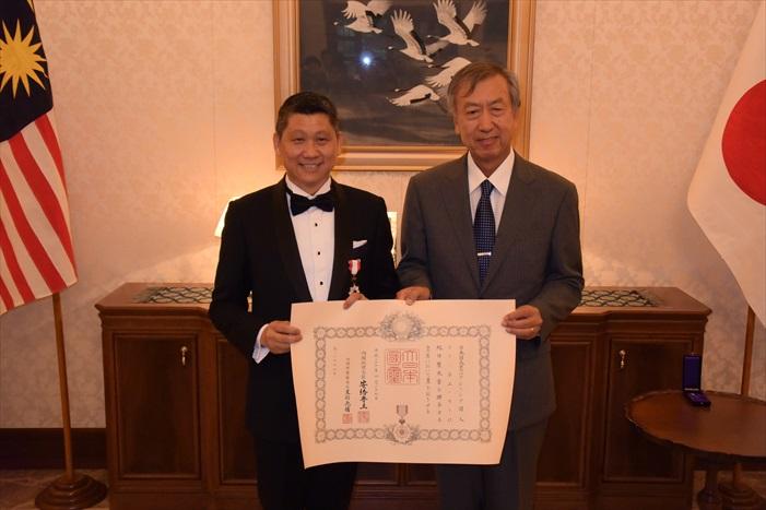 日本驻马大使 宮川 真喜雄(右)代表日本政府,授予蘋果旅遊集团董事经理拿督斯里 李益辉 太平绅士旭日双光章。