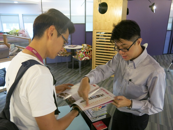 蘋果101执行董事黄引辉向主播庄文杰展示Apple 101出版的旅游刊物。
