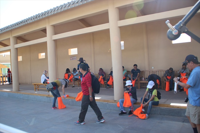 大伙穿上橘色的鞋套,以防沙子灌入鞋子里。