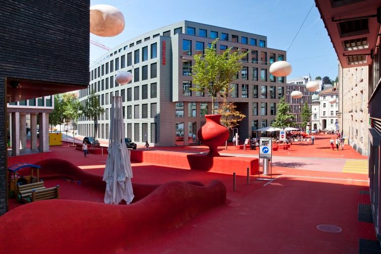 """由两位艺术家联手打造的Stadlounge,把数条街道铺上""""红地毯"""",安置了红桌椅,还有悬挂在空中似明珠的灯,为圣加仑的新城区制造了炽热的话题。"""