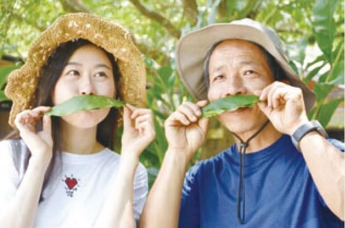 风趣的东风有机休闲农场主人家林文龙(右)与游人一起搞怪。