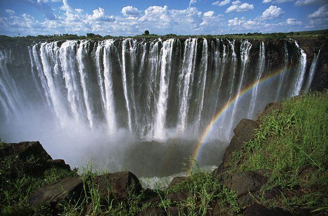 A rainbow forms as the turbulent waters of Zambezi River rush over Victoria Falls. Zimbabwe. ca. 1970-1995 Zimbabwe