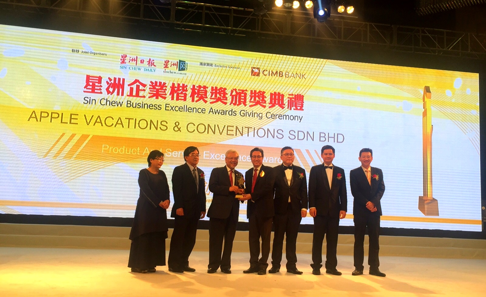 蘋果旅遊集团董事经理拿督斯里许育兴(中)从马来西亚第二财长——拿督斯里阿末胡斯尼(左三)手中接过此荣耀。