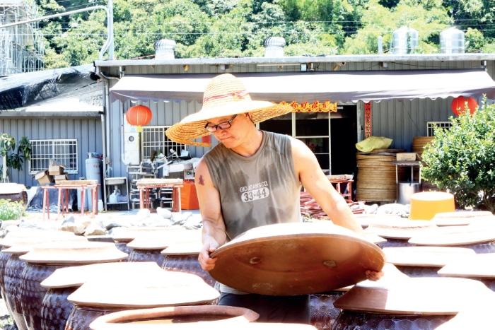 老妈妈手工酱油工坊 顶着艳阳高照,工坊人员逐桶逐桶察看黑豆酱油的发酵情况。
