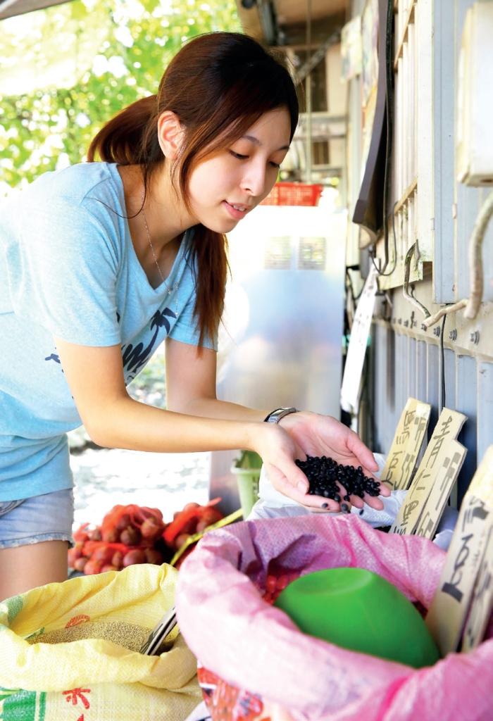 老妈妈手工酱油工坊 工坊人员正在检查工坊外贩卖的农产品,确保新鲜度。