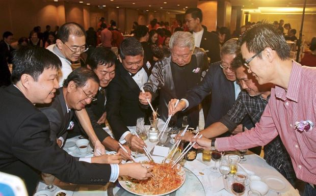Lee (fifth from right) and Chua (fourth from right) tossing yee sang with senior representatives from Apple Vacations.