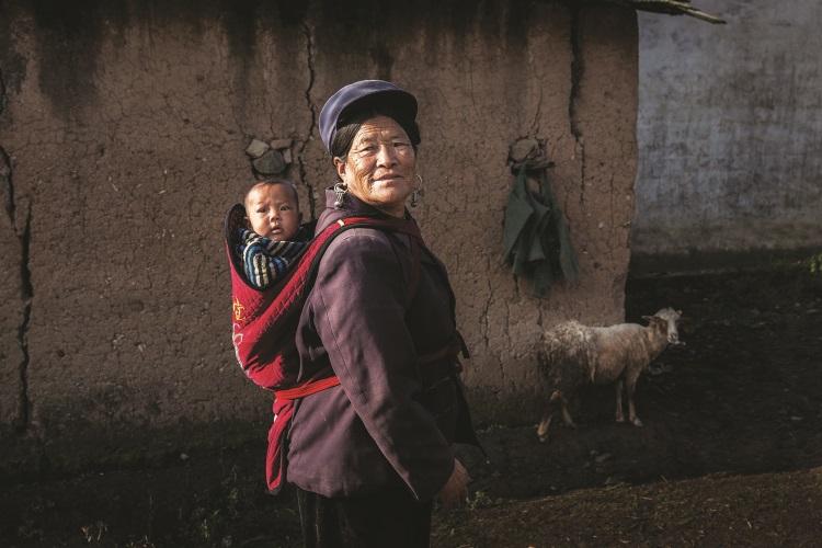 在村里,你能看见很多彝族妇女背着孩子干活。