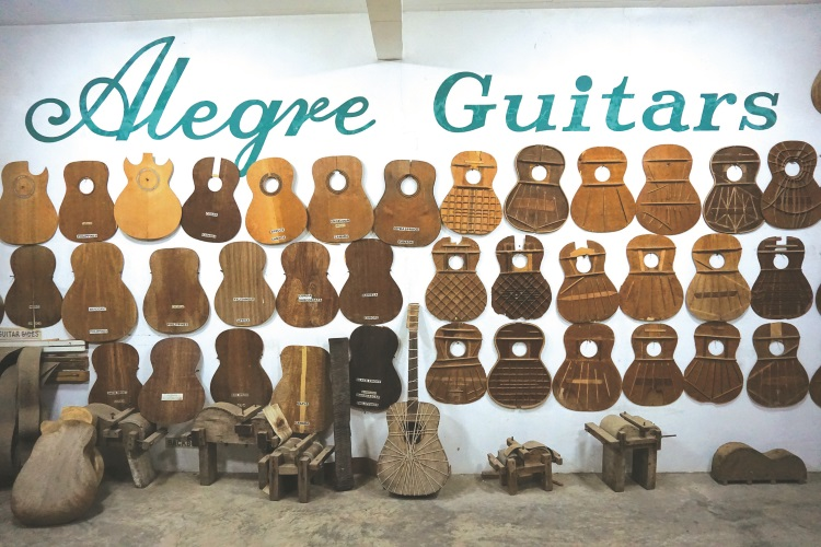 墙上挂满了各式各样的吉他品版,不同吉他款式就有不同的制造方式。