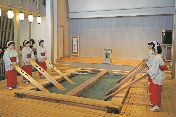 表演者摆动手上的板伴,随着歌声有节奏地搅动温泉水。