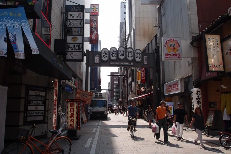 """与道顿堀及相毗邻的宗右卫门町,以前就是商人寻欢作乐的高级区,至今这条""""花街"""",还是日式旅馆、妓馆等交流场所的集中区。这里的街道特色就是以石板路铺成,每当夏季都回一系列热闹活动举行,就如""""夏季的麦酒节"""",""""宗右卫门町夏日祭""""就是以美食加美酒让这条街更具特色。"""