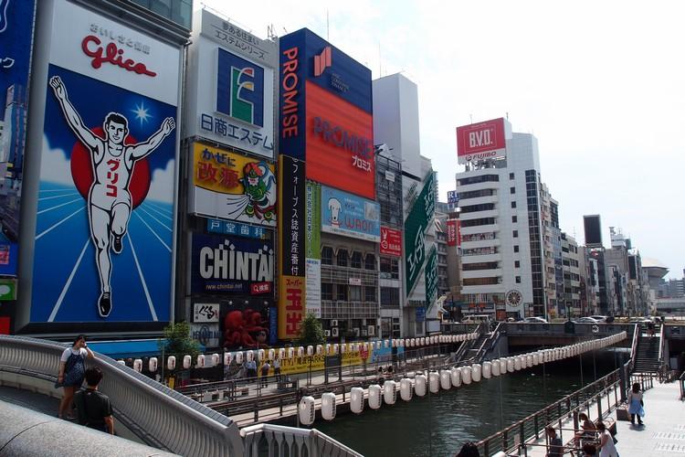 """大阪最具形象的招牌 -- """"格力高(Glico)跑步者"""", 许多游客会学者本尊摆着同样的姿势拍照。"""