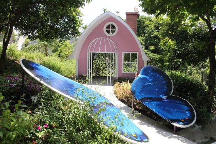 精致小而美的粉红小屋盖在花海中,让游客可透过墙上的百孔赏蝶,避免对蝴蝶造成伤害。
