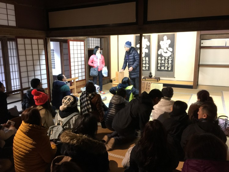 大伙在高山阵屋里听讲解员讲解,导游则在旁做翻译。
