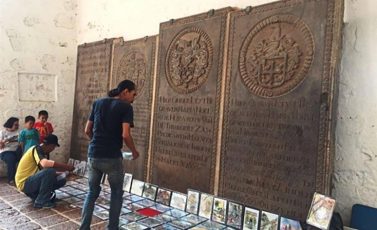 The historical engraved slabs at St Paul's Church in Malacca are treated as props by vendors for their souvenirs. (Photos: Leesan)