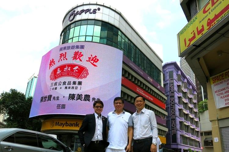 三叔公食品集团贵宾:陈美农(右)及 陈世宝(中)在蘋果大楼LED屏幕前和蘋果101执行董事黄引辉合影。