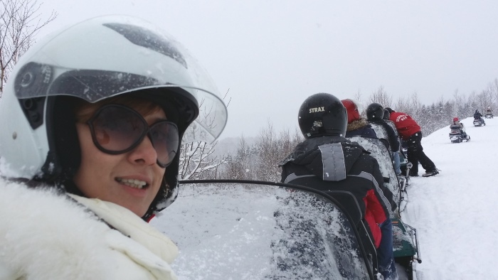 乘坐在行程安排的雪上摩托车的Chui Ling。