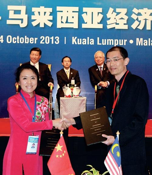 中国观印象艺术发展公司总执行长王潮歌(左)与PTS董事长巫光伦签约:习近平(后左)与纳吉(后右)见证
