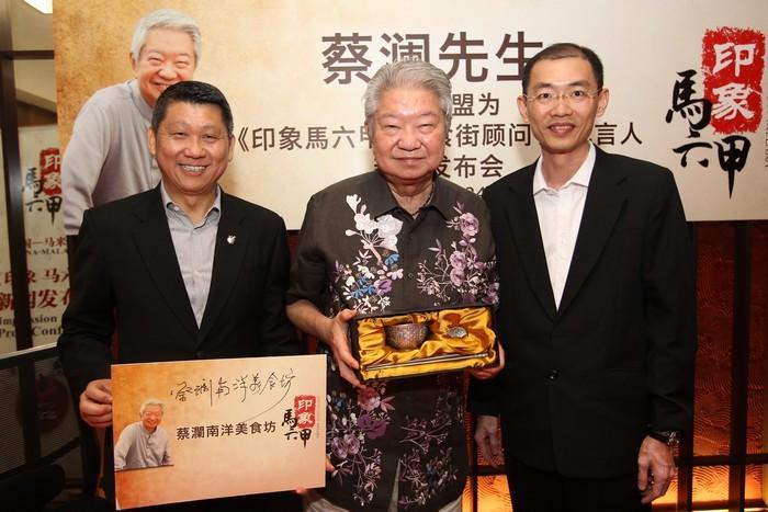 《印象马六甲》首席执行员巫光伦(右)赠送纪念品给蔡澜先生。左为蘋果旅遊集团董事经理拿督斯里李益辉太平绅士(李桑)