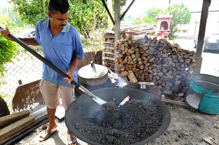 工人以橡胶木材生火,和以粗盐翻炒盐焗鸡。