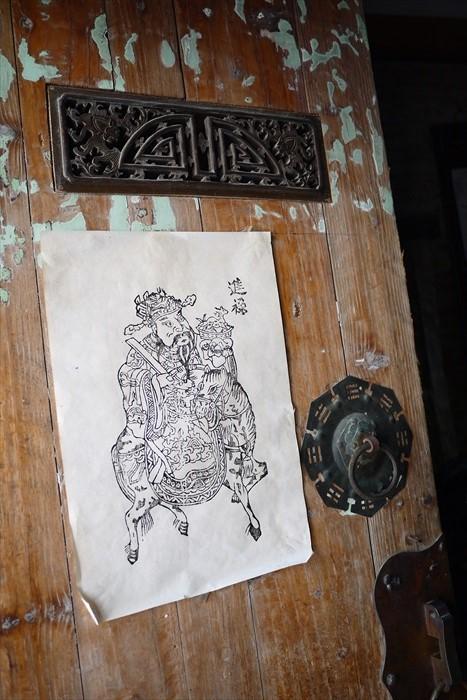 木造门框上飞舞的斑漆痕跡,显露了老屋的年龄。