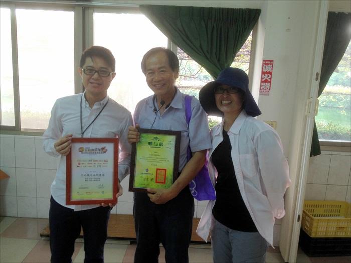 最后,由台湾休闲农业发展协会行销总监邱翔羚(右)与蘋果101执行董事黄引辉(左)颁赠纪念装给台南鸭庄休闲农场场长苏清发。