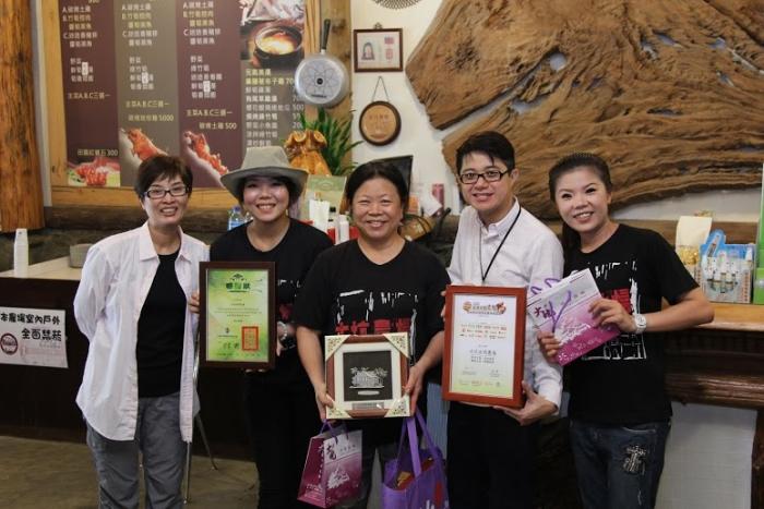 台湾休闲农业发展协会行销总监邱翔羚(左1)与蘋果101执行董事黄引辉(右2)颁赠纪念装给亲切蔡家家族。