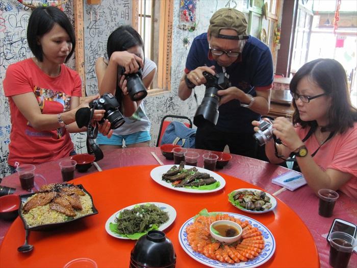 蛤仔辉特产中心的食料以蛤为主,媒体在拍摄桌上的美食。