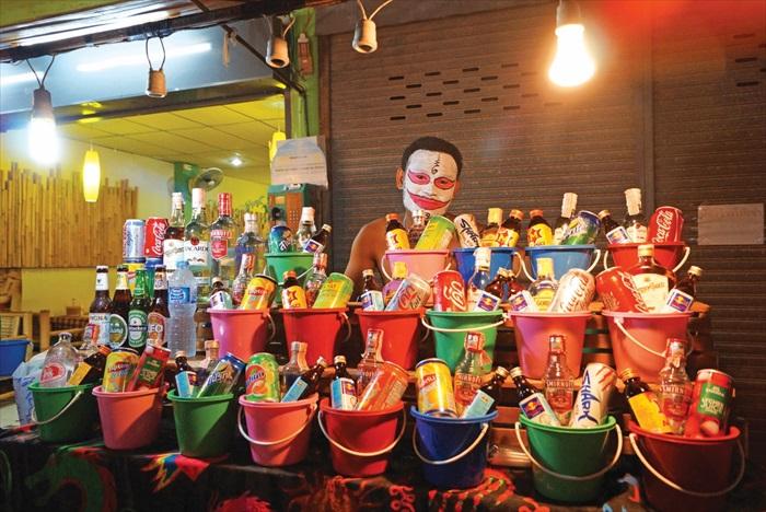 售卖饮料的摊贩也来参一脚,脸上绘着奇幻图案吸引客人上门,桌上一桶桶的就是所谓的鸡尾酒了。