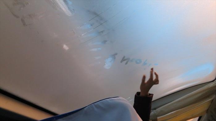 冬天的车厢内,小女孩在车窗上写字。我猜,她是想念某个人了。