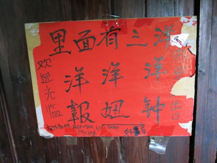 """土楼墙上贴着楷书广告,我看不懂中间那个""""产品""""为何物..."""