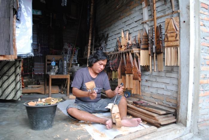 一家纪念品店里,巴塔克人在认真的雕刻木头。